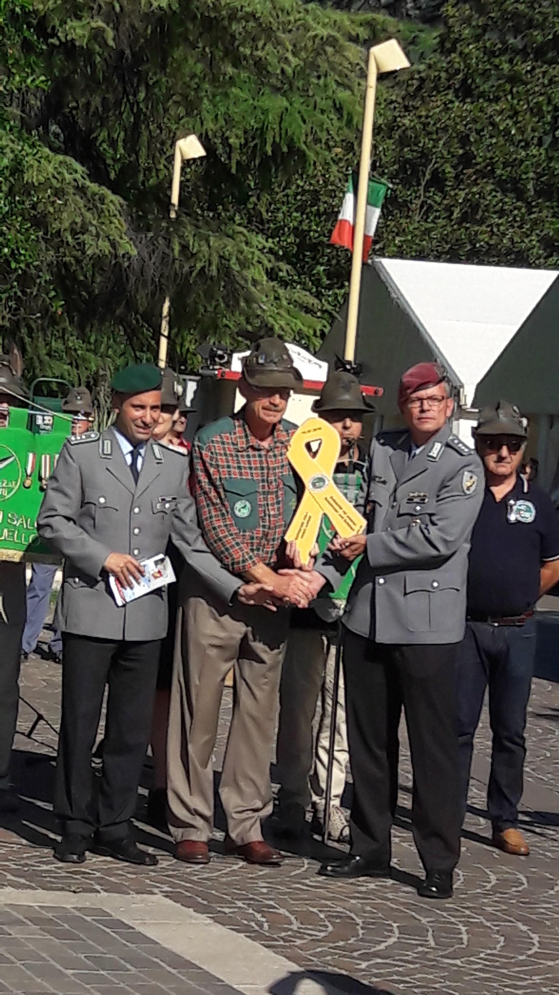 """Hauptmann Martin Würtz (rechts) und sein Stellvertreter Hauptmann d. R. Marcello Camerin (links) übergaben Carlo Zanoni die """"gelbe Schleife"""" der Solidarität."""